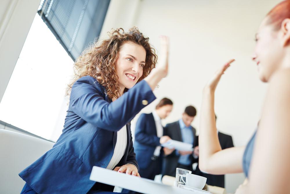 Twee zakenvrouwen geven elkaar een high five als zijnde het winnende team[:]