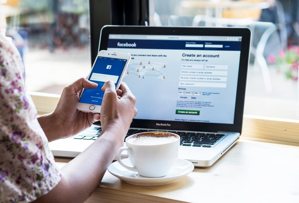 verschil tussen een Facebook-pagina en een Facebook-groep? - scherm met facebook en telefoon - wanneer is het slim om te adverteren op Facebook